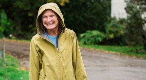 Julie Wolcott shown outside in raincoat with hood up, smiling.